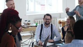 Счастливые усмехаясь коммерческие директоры работают совместно, сотрудничают с мужским боссом сидя на таблице офиса просторной кв видеоматериал