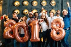 Счастливые усмехаясь люди держа золотой номер раздувают, символ 2018 год Стоковая Фотография