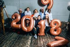Счастливые усмехаясь люди держа золотой номер раздувают, символ 2018 год стоковые изображения rf
