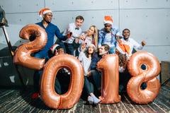 Счастливые усмехаясь люди держа золотой номер раздувают, символ 2018 год Стоковое Фото