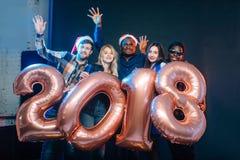 Счастливые усмехаясь люди держа золотой номер раздувают, символ 2018 год Стоковые Фотографии RF