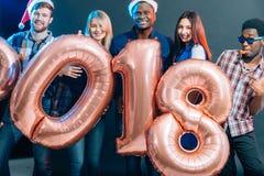 Счастливые усмехаясь люди держа золотой номер раздувают, символ 2018 год стоковые фото