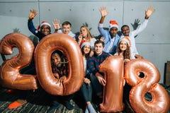 Счастливые усмехаясь люди держа золотой номер раздувают, символ 2018 год стоковое изображение