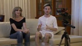 Счастливые усмехаясь молодые пары с сообщением записи камеры видео- для vlog дома на кресле - сток-видео