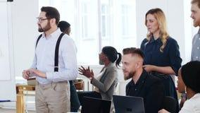 Счастливые усмехаясь профессиональные многонациональные коллеги работают совместно, обсуждают проект на современной встрече конфе видеоматериал