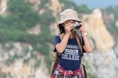 Счастливые усмехаясь рюкзак девушки кавказских детей азиатские и камера держать для принимают фото проверяют внутри на горе Стоковое Изображение RF