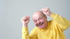 Счастливые успешные пенсионер или бизнесмен выигрывая, кулаки нагнетали праздновать изолированную успехом серую предпосылку стены видеоматериал