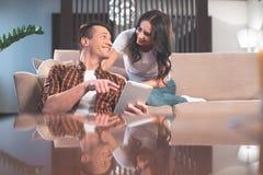 Счастливые человек и женщина используя таблетку в живущей комнате Стоковые Изображения RF
