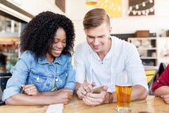 Счастливые человек и женщина с smartphone на баре Стоковые Фото