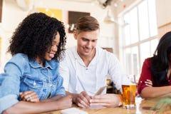 Счастливые человек и женщина с smartphone на баре Стоковое Изображение