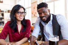 Счастливые человек и женщина с smartphone на баре Стоковые Изображения
