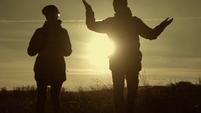 Счастливые человек пар и турист женщины наверху горы на заходе солнца outdoors во время похода Силуэты 2 hikers с видеоматериал