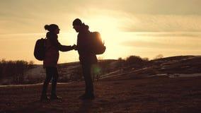 Счастливые человек пар и турист женщины наверху горы на заходе солнца outdoors во время похода Силуэты 2 hikers с сток-видео