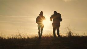 Счастливые человек пар и турист женщины наверху горы на заходе солнца outdoors во время похода Силуэты 2 hikers с акции видеоматериалы