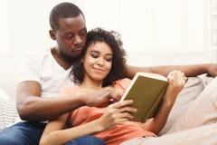 Счастливые черные пары читая совместно дома Стоковая Фотография