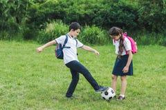 счастливые школьники играя футбол совместно на луге стоковые фото