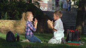 Счастливые школьники играя хлопающ игра сидя в природе после уроков на перерыве школы сток-видео