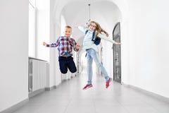 Счастливые школьники представлять, скача в школу стоковые изображения rf