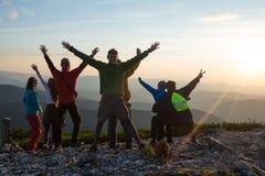 Счастливые hikers, друзья с открытыми оружиями стоят на верхней части Стоковая Фотография