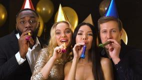 Счастливые multiracial друзья в b-дневных шляпах дуя в ticklers партии, торжестве видеоматериал