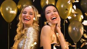 Счастливые multiracial женщины усмехаясь и имея потеху на партии под падая confetti сток-видео