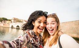 Счастливые multiracial подруги принимая selfie и имея outdd потехи Стоковое фото RF