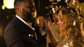 Счастливые multiracial танцы под падая confetti, торжество человека и женщины акции видеоматериалы