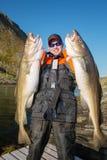 Счастливые pokazyvaetes рыболова 2 больших рыбы в их руках Vertic Стоковое фото RF