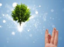 Счастливые smileys пальца с зеленым волшебным накаляя деревом Стоковая Фотография
