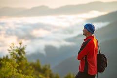 Счастливый авантюрист на верхней части горы во время захода солнца Стоковые Фотографии RF
