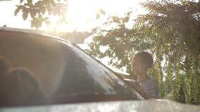 Счастливый азиатский автомобиль стирки девушки на брызгать и солнечном свете воды дома видеоматериал