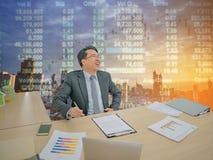 Счастливый азиатский бизнесмен сидя на его столе с фондовой биржей o стоковые фото
