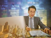 Счастливый азиатский бизнесмен сидя на его столе с фондовой биржей o стоковые изображения