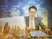 Счастливый азиатский бизнесмен сидя на его столе с фондовой биржей o стоковые фотографии rf