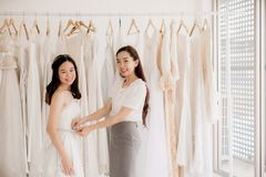Счастливый азиатский дизайнер женщин делая регулировку в студии моды, азиатской невесте smling и пробуя на платье свадьбы стоковая фотография rf