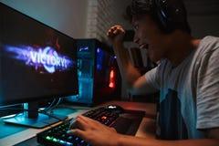 Счастливый азиатский мальчик gamer выигрывая пока играющ видеоигры на compu стоковая фотография rf