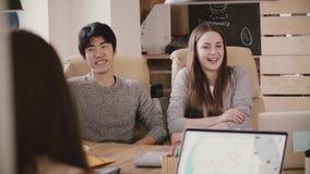 Счастливый азиатский молодой человек и европейская девушка сидят таблицей, улыбкой и болтовней слушая к речи босса в современном  сток-видео