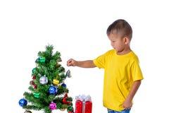 Счастливый азиатский ребенок держа меньший колокол для рождества t украшения стоковая фотография
