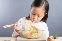 Счастливый азиатский ребенок есть очень вкусную лапшу Стоковые Изображения RF