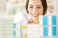 Счастливый аптекарь ища медицину в фармации Стоковое Фото