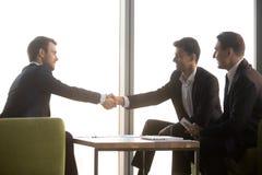 Счастливый арабский и кавказские бизнесмены тряся руки на встрече стоковые фото