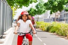 Счастливый африканский велосипед катания девушки на пути цикла Стоковая Фотография RF