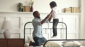 Счастливый африканский отец играя с сыном ребенк скача на кровать видеоматериал