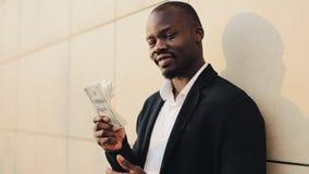 Счастливый Афро-американский бизнесмен держа большую сумму денег в его руках Он стоит в улице около офиса видеоматериал