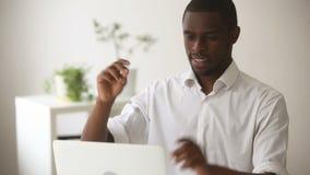 Счастливый Афро-американский бизнесмен чувствует расслабленную конторскую работу отделкой на компьтер-книжке сток-видео
