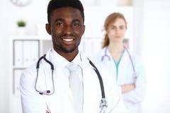 Счастливый Афро-американский мужской доктор с медицинским персоналом на больнице стетоскоп дег микстуры лож принципиальной схемы  стоковое изображение