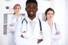 Счастливый Афро-американский мужской доктор с медицинским персоналом на больнице стетоскоп дег микстуры лож принципиальной схемы  стоковые фотографии rf
