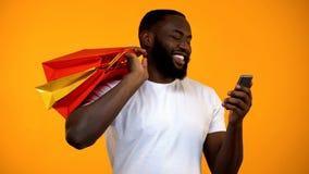 Счастливый Афро-американский человек держа хозяйственные сумки и смартфон, онлайн приобретение стоковое фото