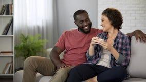 Счастливый Афро-американский человек наблюдая его счастливую коробку отверстия девушки с подарком стоковые изображения rf