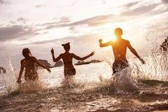 Счастливый бег пляжа моря захода солнца друзей стоковое фото rf